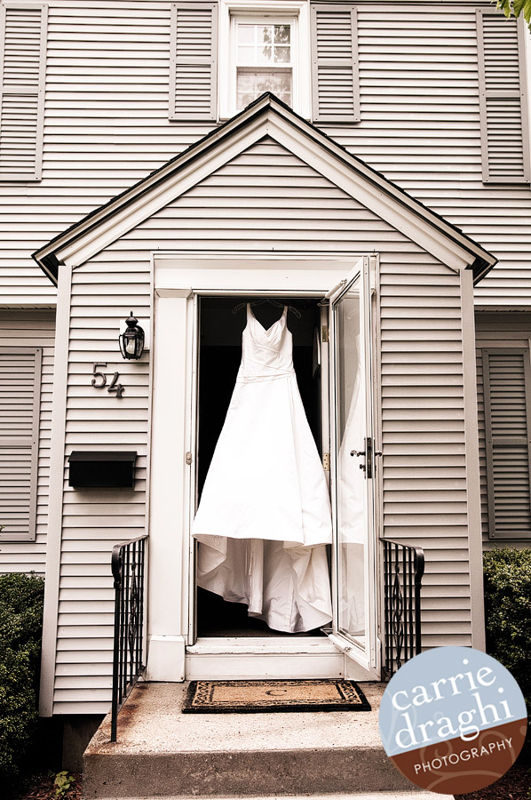 bride's wedding dress hanging from door