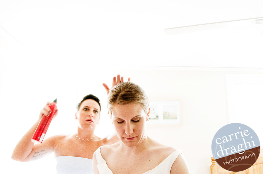 bride getting hair sprayed by sister